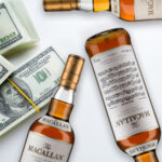 bottles of macallan archival series and stacks of $100 bills