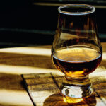 a Glencairn glass of scotch with shadow and light