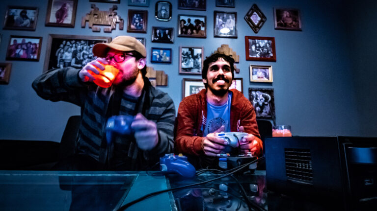 Two men play a video game with drinks by their side