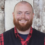 Bearded man smiles in front of wood planks in the background