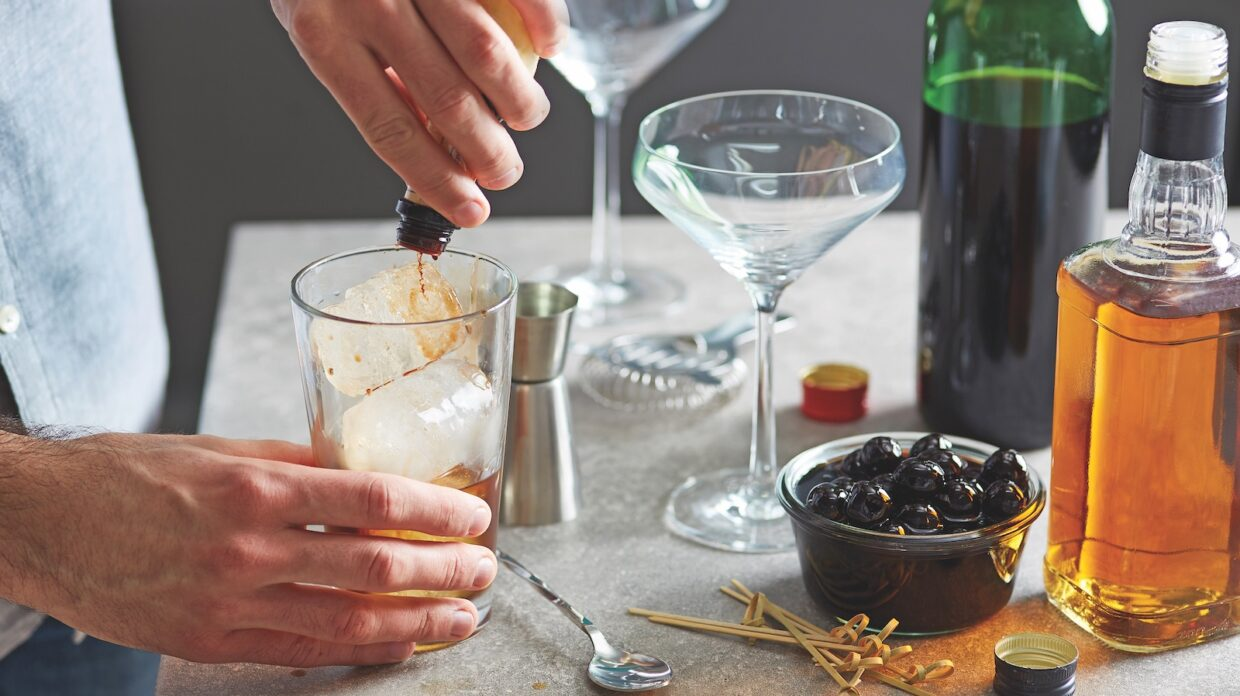 Close-up of bartender preparing Manhattan cocktail while adding bitter into glass of ice.