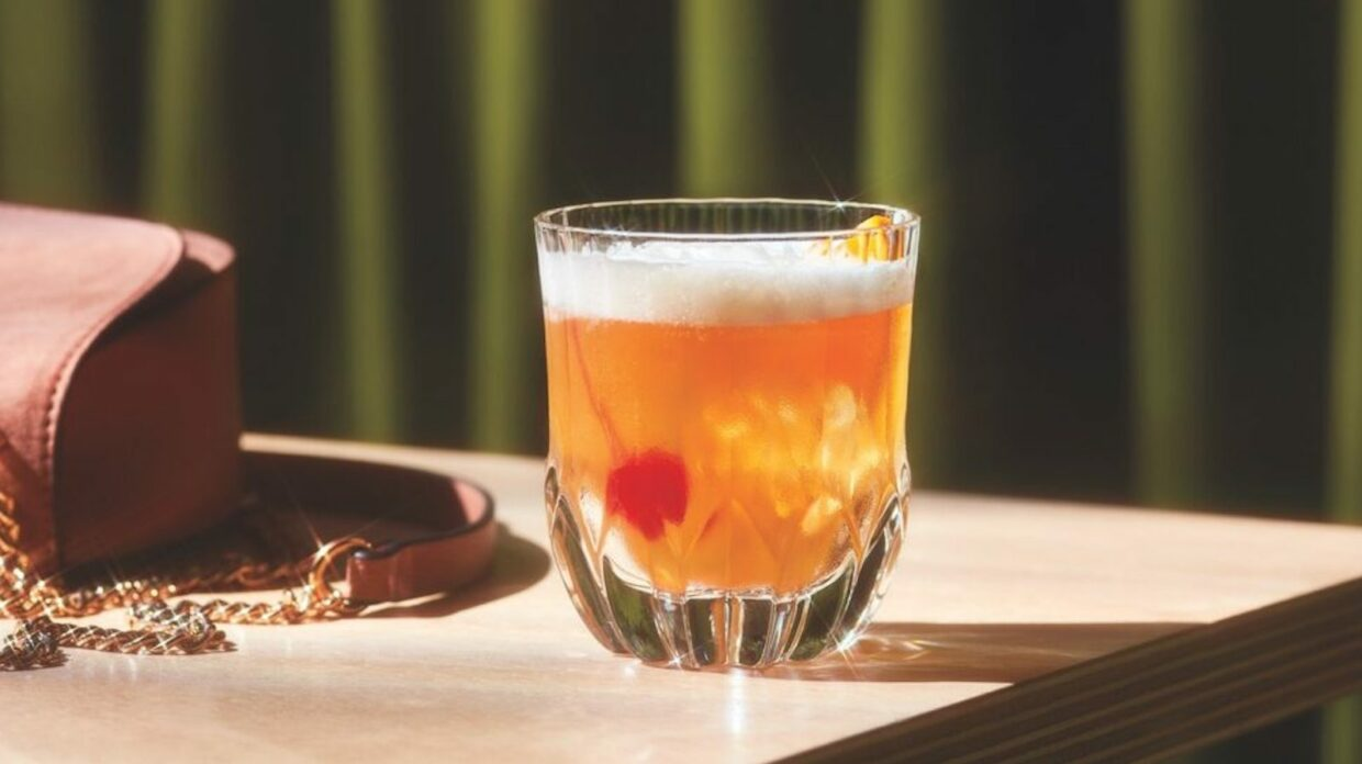 Whiskey sour cocktail on a wooden table with a green background