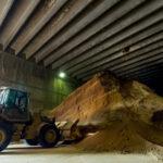 a bulldozer moves a mountain of grain