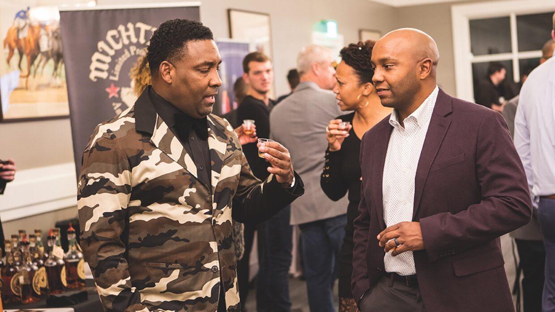 Two men taste whisky together at an event.
