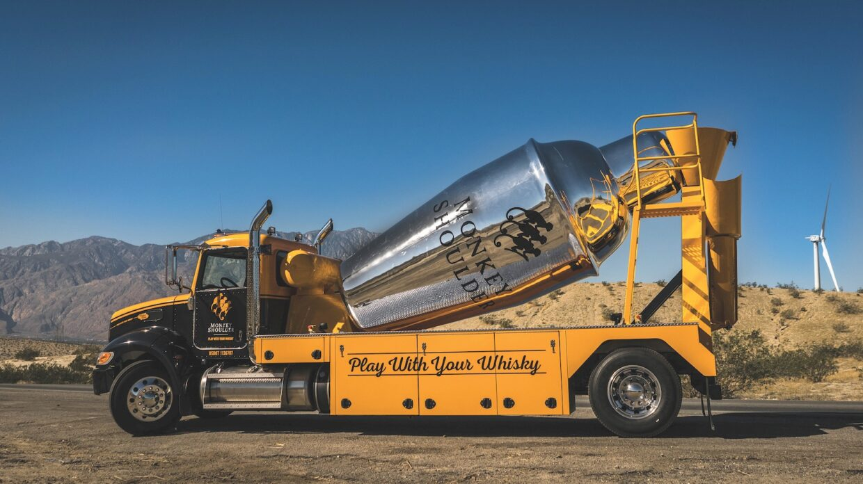 A flatbed truck holds a large metallic cocktail shaker in the style of a cement truck.