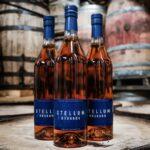 three bottles of stellum bourbon on a barrel