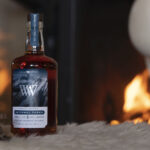 A bottle of whiskey rests on fur with a fire in the background.