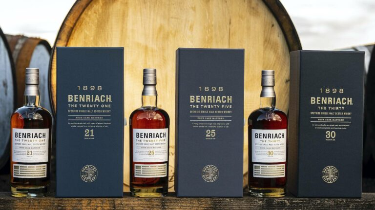 Three bottles of whisky and their display boxes positioned in front of a barrel head