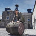 A man rolls a barrel outside a distillery