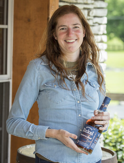 A woman poses with a bottle of whiskey.