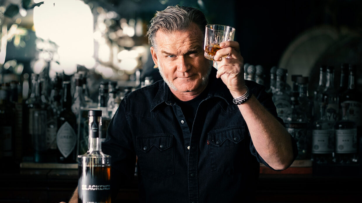 A man stands behind a bar and holds up a glass of whiskey