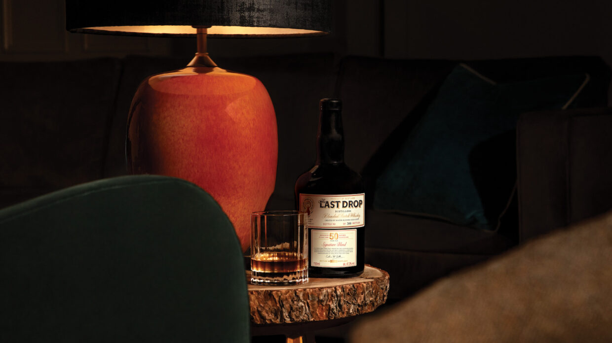 A bottle of whisky and glass of whisky sit on a table under low light.