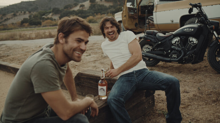 Two men sit outside and share a laugh and a bottle of whiskey