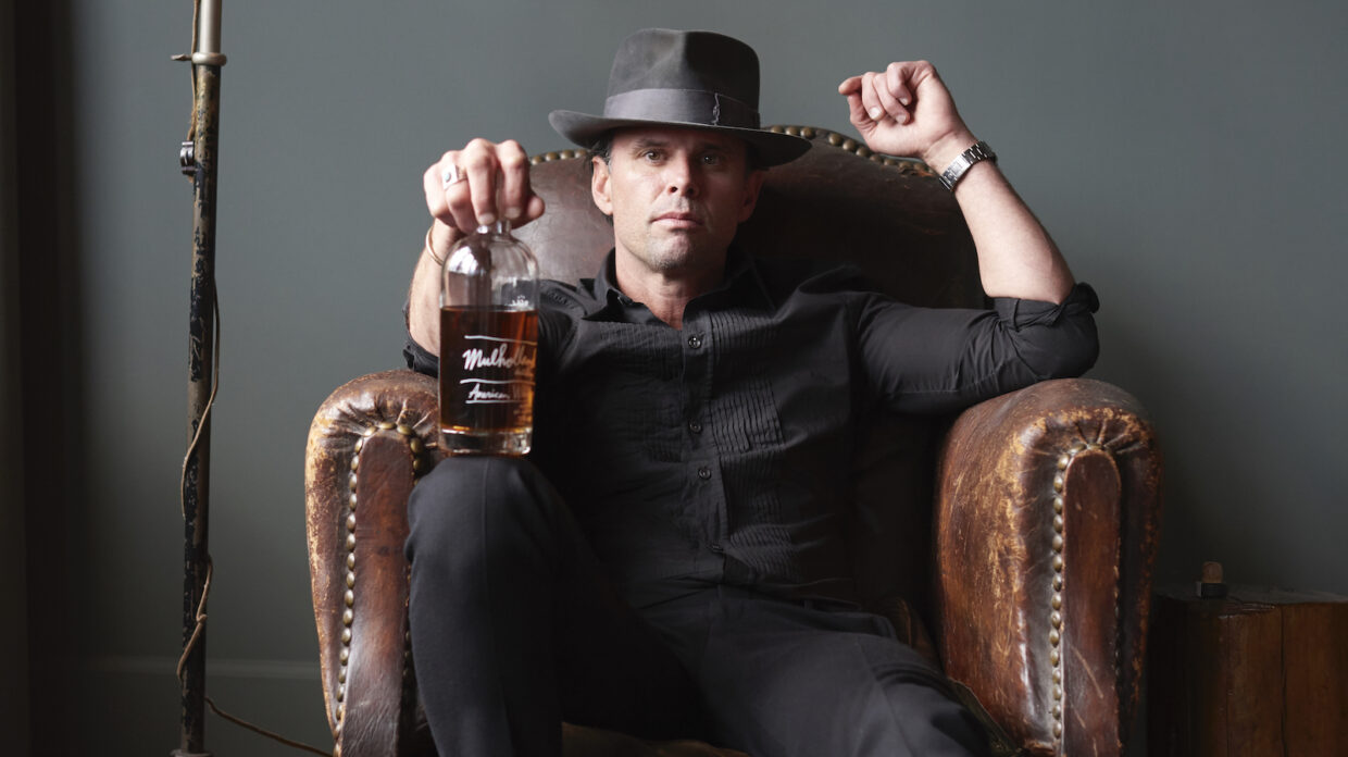 A man sits on a leather arm chair with a bottle of whiskey