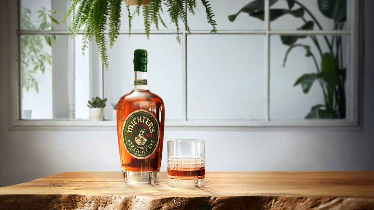 bourbon bottle and glass with some whiskey on a wooden table