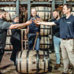 Whisky makers touch glasses over a barrel