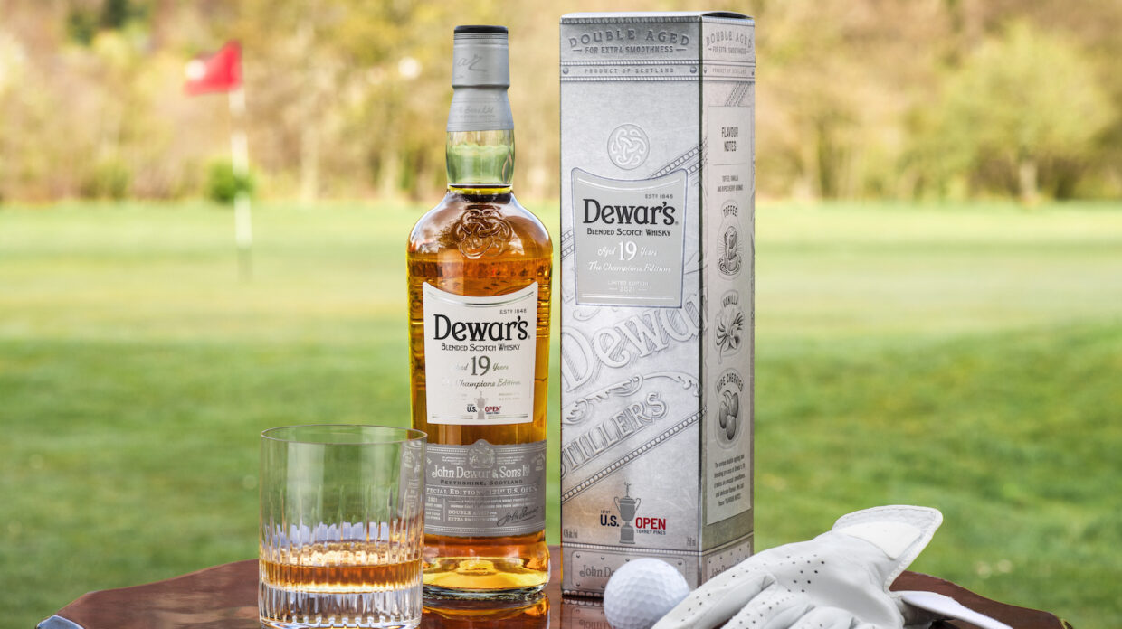 Whisky bottle and glass, half ball and gloves, on a golf course