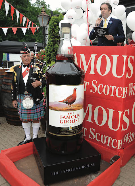 Man standing next to a very tall bottle of whisky