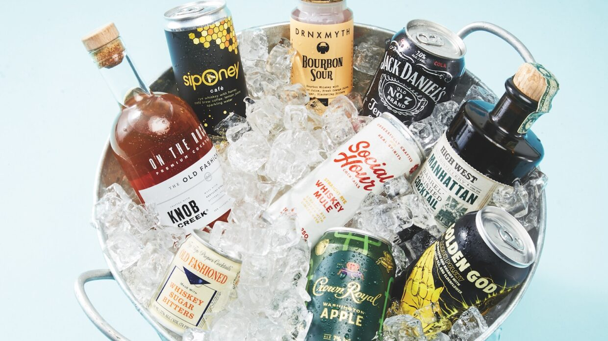 Various canned and bottled cocktails sitting in an ice bucket