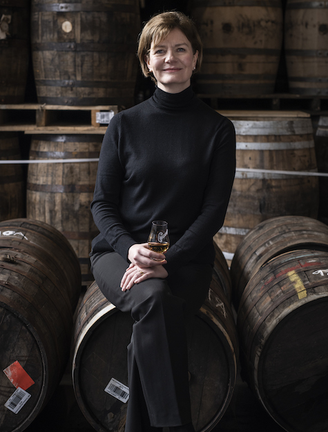 A woman sits on a whiskey barrel