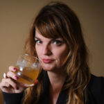 Woman poses with a whiskey glass