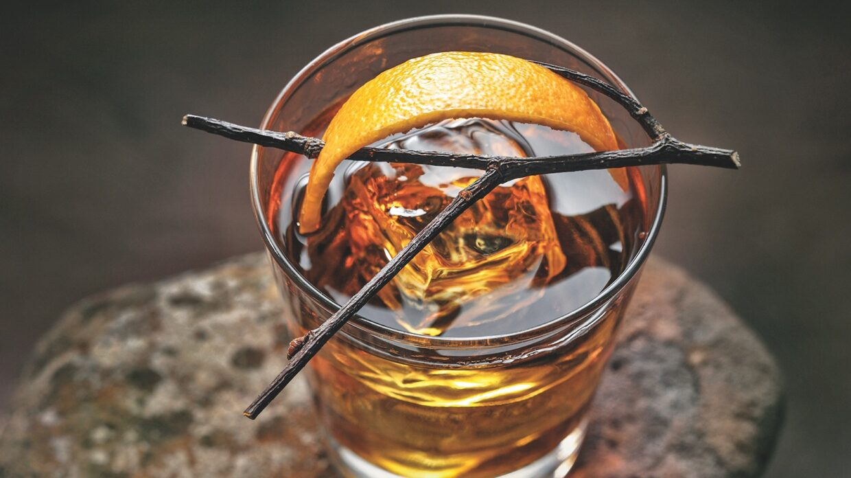 Cocktail with a stick and orange peel garnish