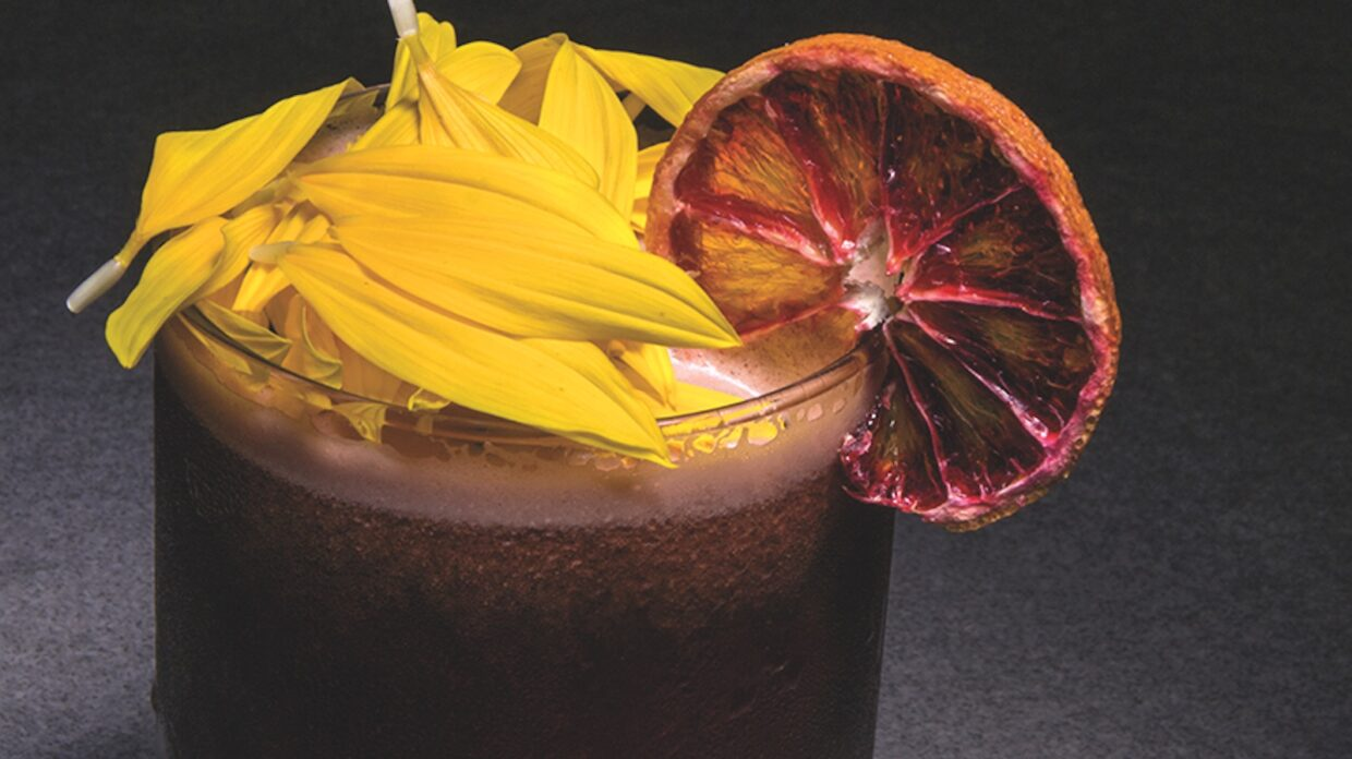 A cocktail with an flamed orange disc garnish
