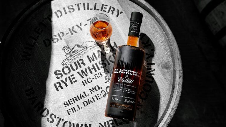 bottle of whiskey lying on a barrel