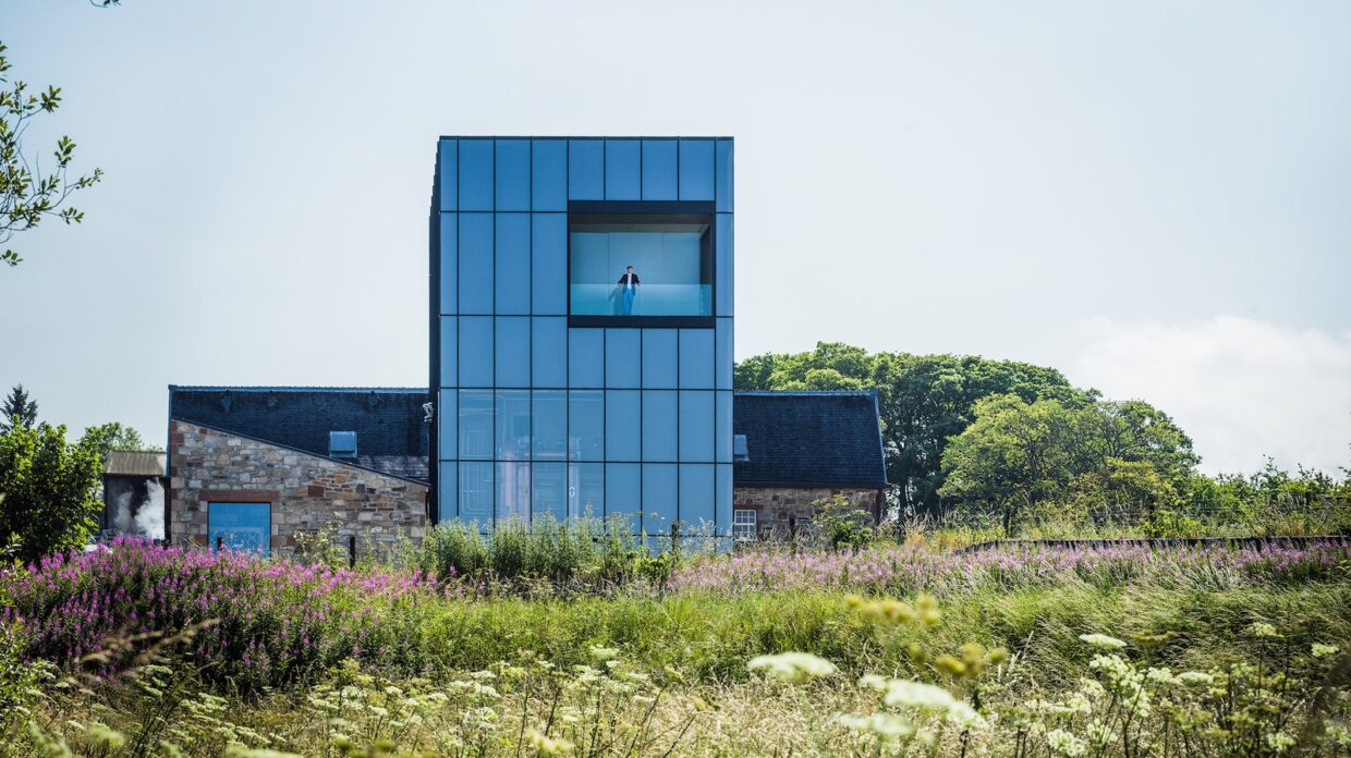 A tall glass building in the Scottish countryside