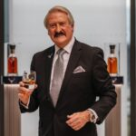 A man in a suit holds a whisky glass