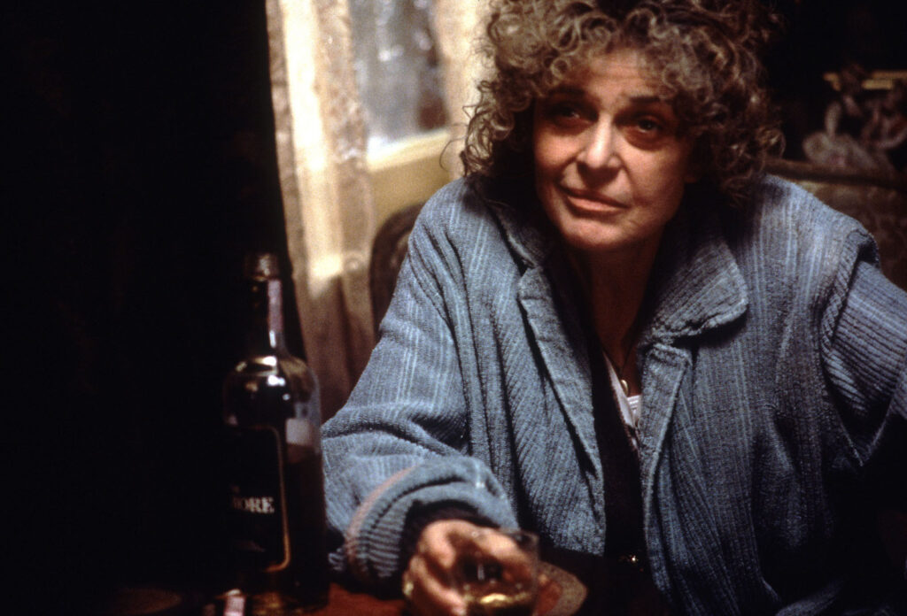 Woman in a bathrobe with a glass of whisky
