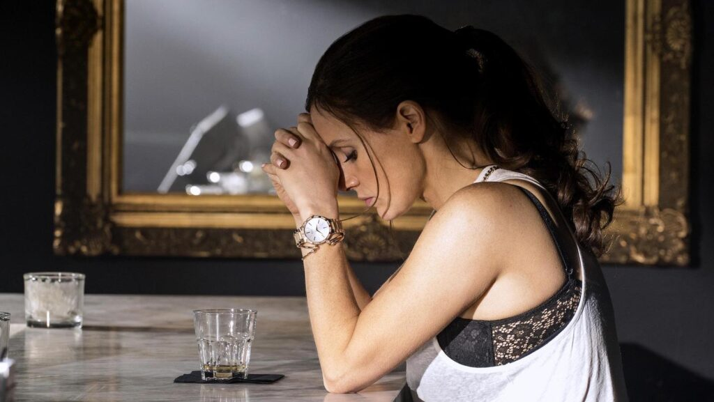 Woman at a bar with an empty glass of whisky