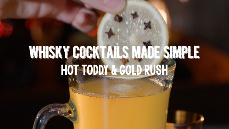 Clove studded lemon is placed into a whiskey drink