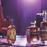 Bottles of whiskey on a stage with a guitar and amplifier