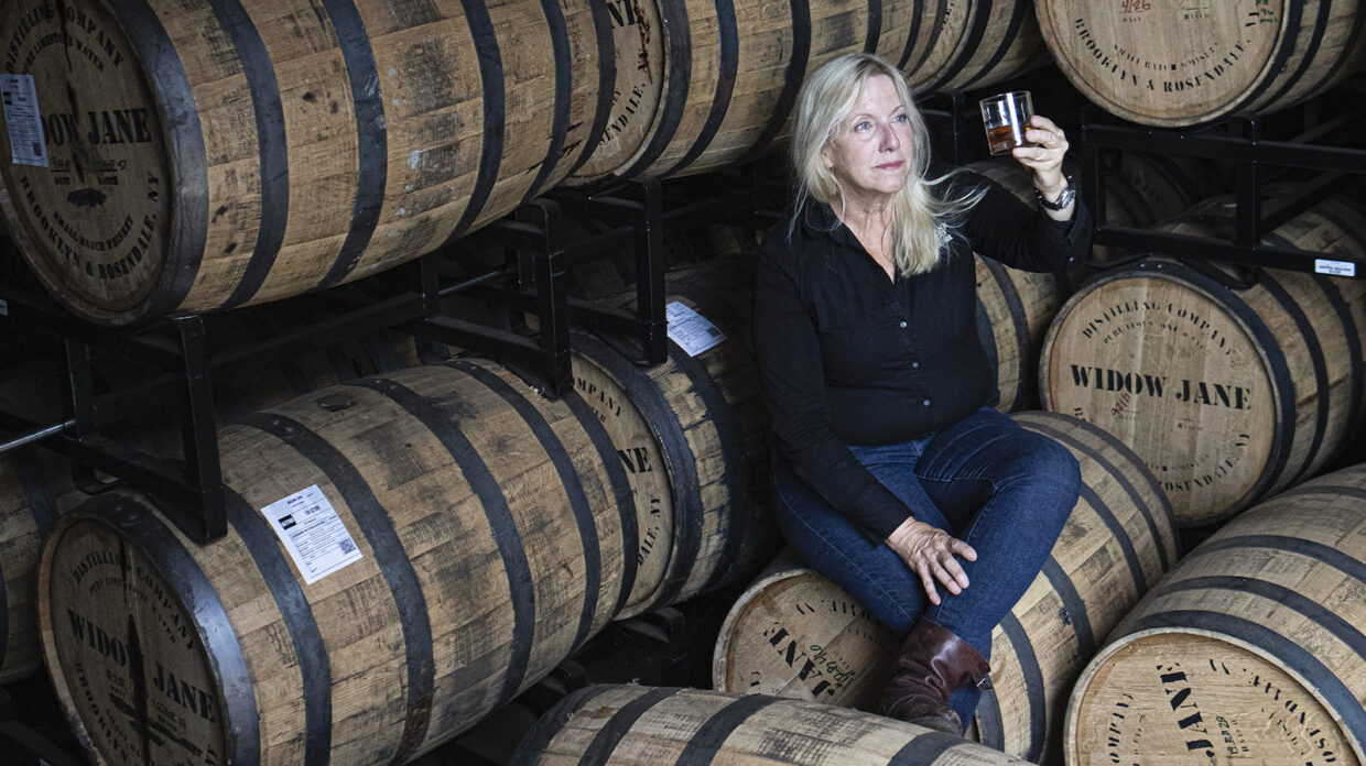 A woman looks at a whisky glass in a barrel house